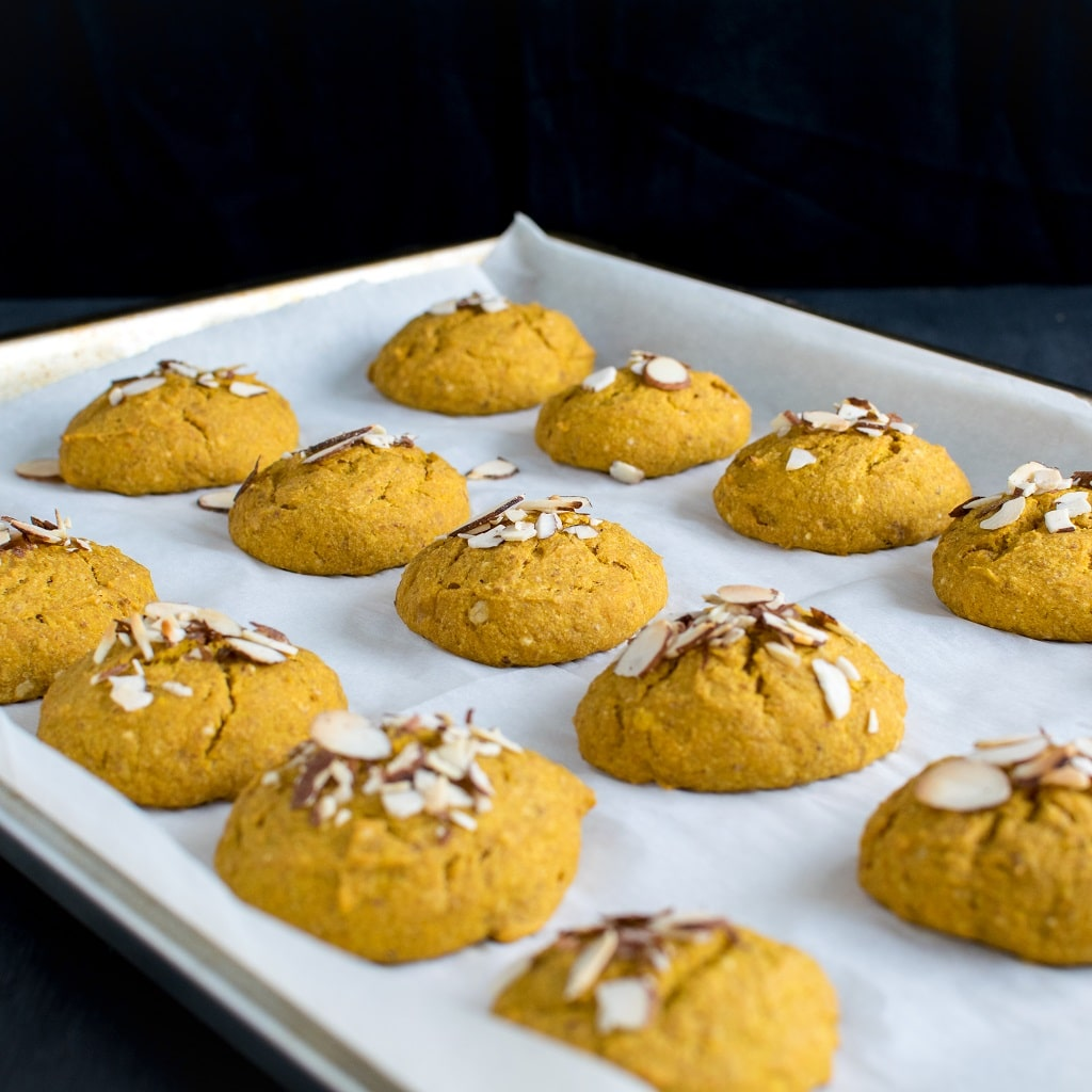Almond Butter Pumpkin Oatmeal Cookies are shown on a cookie sheet fresh out of the oven. The cookie sheet is covered with a parchment paper and the cookies are beautifully spread over it [ vegan + oil free ] kiipfit.com