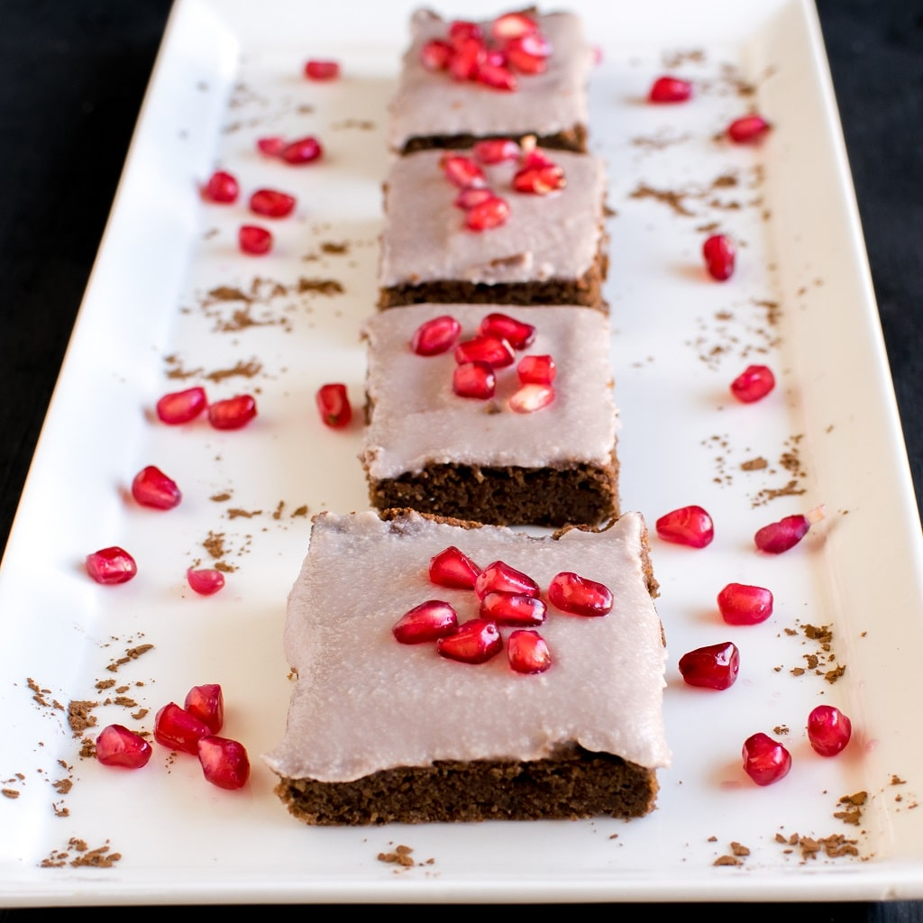 Pomegranate Frosted Flourless Brownies placed in a serving plate in a line with a focus on the first brownies. The white serving long rectangle plate is decorated with pomegarante kernels and chocolate powder [ vegan + paleo + gf ] kiipfit.com