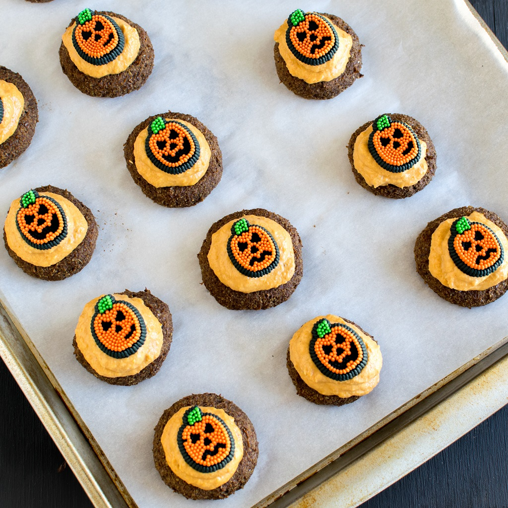 Frosted Pumpkin Cheesecake Coffee Flax Cookies with pumpkin frosting along with cute pumpkin face decorations [ vegan + GF ] kiipfit.com