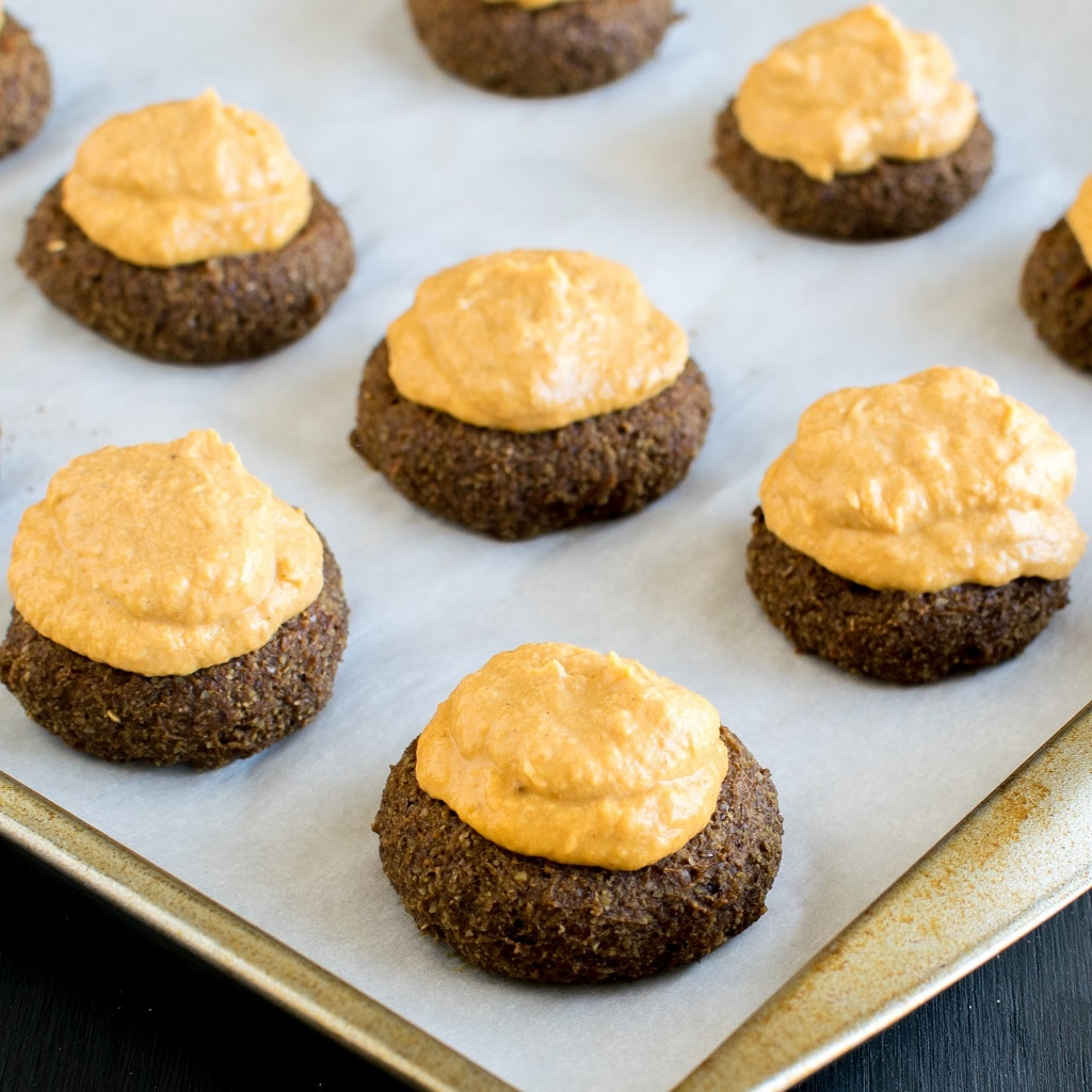 Frosted Pumpkin Cheesecake Coffee Flax Cookies with pumpkin pumpkin frosting on a cookie sheet [ vegan + GF ] kiipfit.com