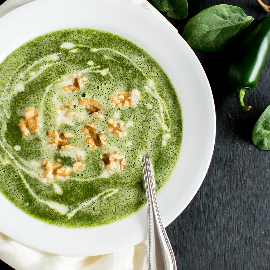 Top view of Fire Roasted Jalapeno Pear Spinach Soup in a white bowl topped with walnuts and cashew cream and a spoon inserted in the soup [ vegan + paleo ] kiipfit.com