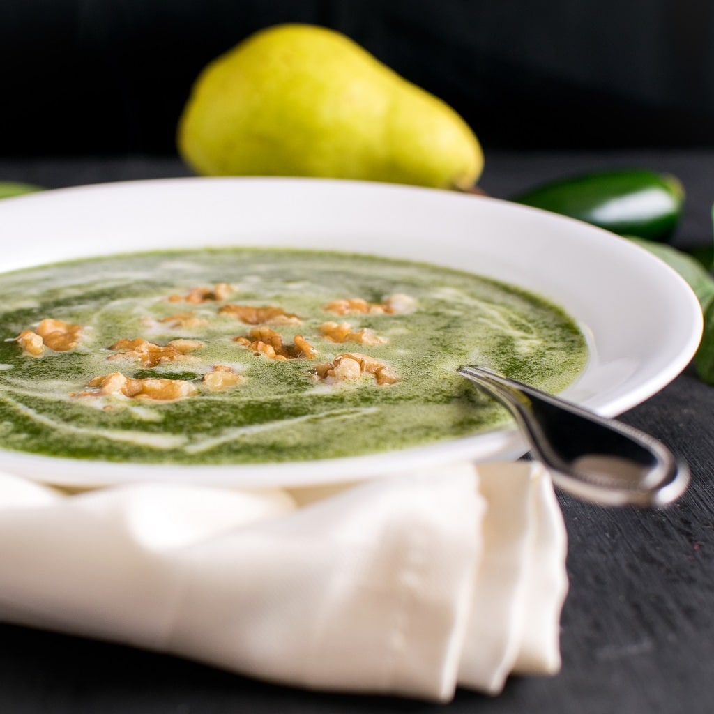 Fire Roasted Jalapeno Pear Spinach Soup in a white bowl from the front angle. A spoon is inserted in the soup from the viewers side and it has green pear, some spinach leaves and a jalapeno pepper in the background [ vegan + paleo] kiipfit.com