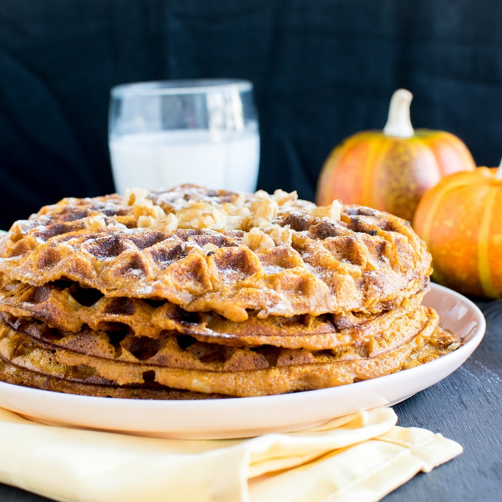 Pumpkin Pie Spice Spelt Waffles on a pink dessert plate. The image appears from the front angle showing the stack of waffles with a glass of milk and couple of pumpkins on the background [ vegan ] kiipfit.com