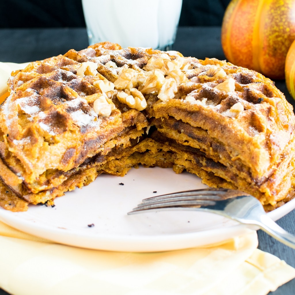 Pumpkin Pie Spice Spelt Waffles cut into a triangle slice on a pink dessert plate with a fork on the plate too. The waffles are covered with powdered sugar and topped with raw walnuts [ vegan ] kiipfit.com
