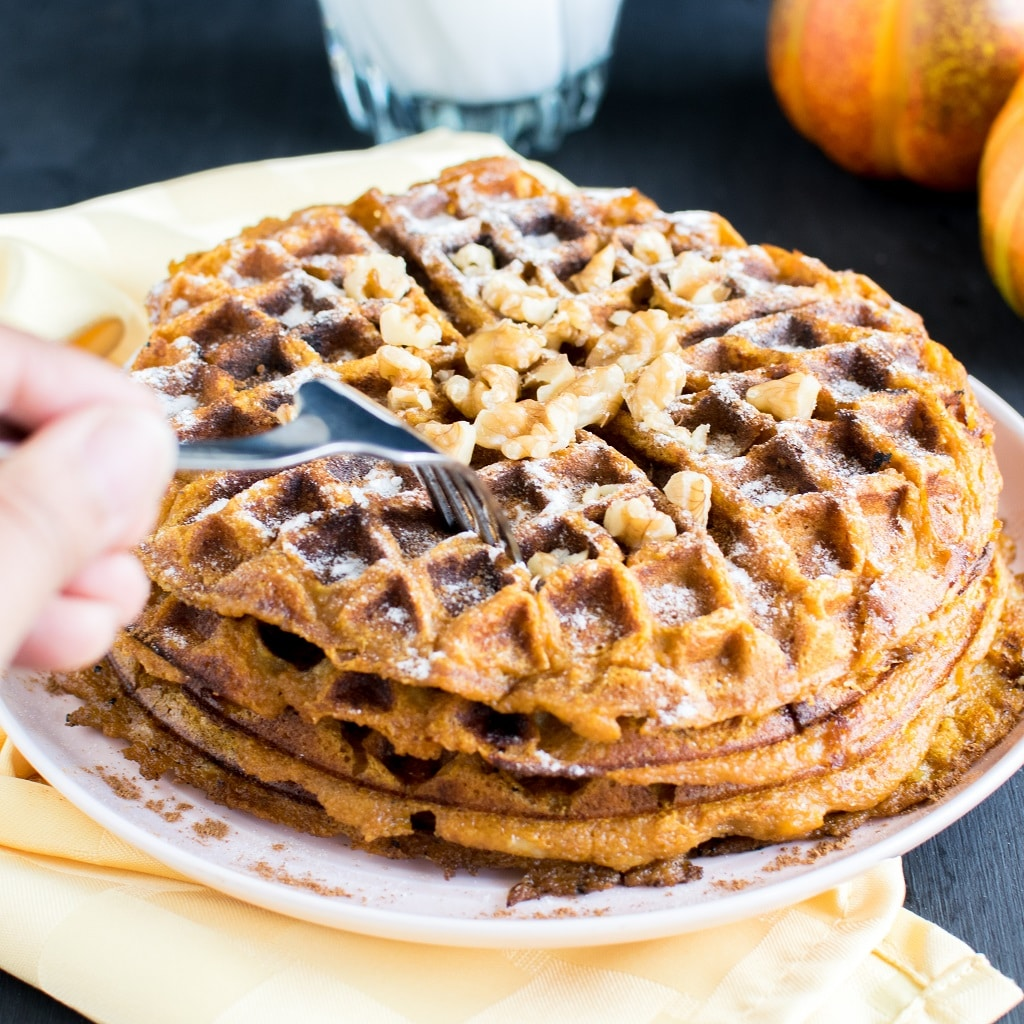 Pumpkin Pie Spice Spelt Waffles covered with powdered sugar and topped with walnuts. This image is showing a hand holding a fork and trying to cut out a slice of the waffles [ vegan ] kiipfit.com