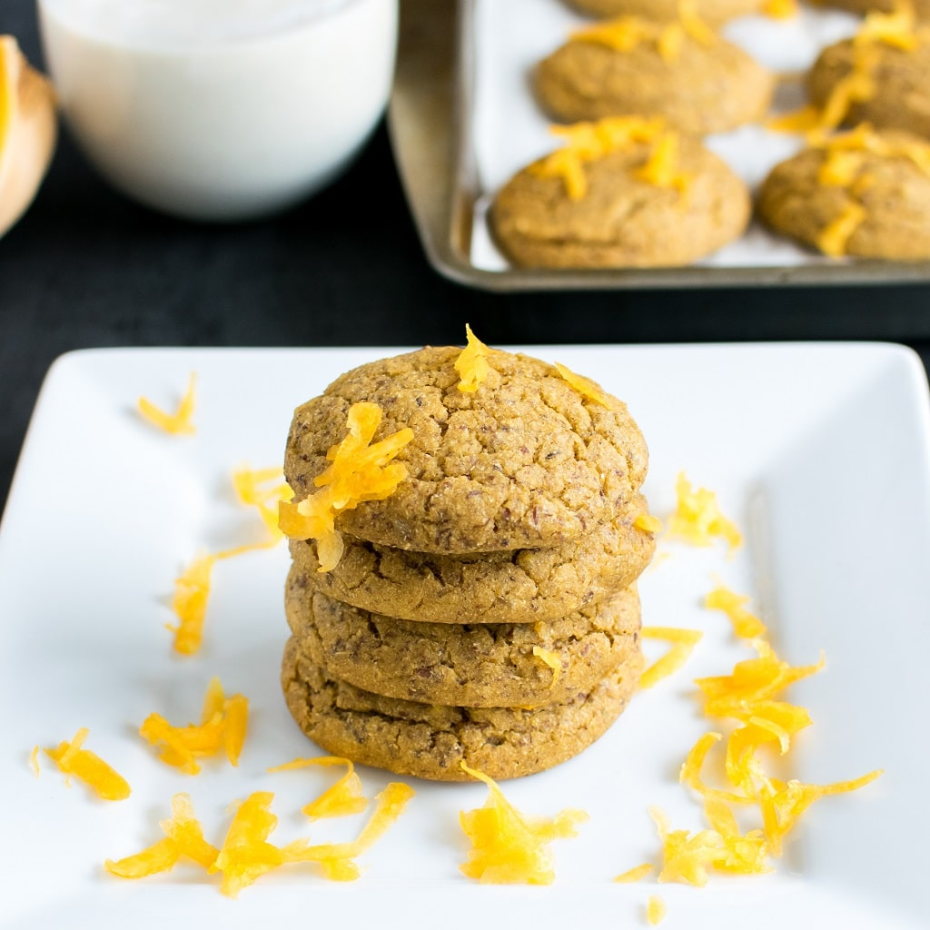 Butternut Squash Barley Vegan Cookies are stacked on a white square plate. These cookies are decorated with shaved squash and have the fruit and a glass of milk along with a cookie sheet filled with cookies at the background [ oil free + nut free ] kiipfit.com