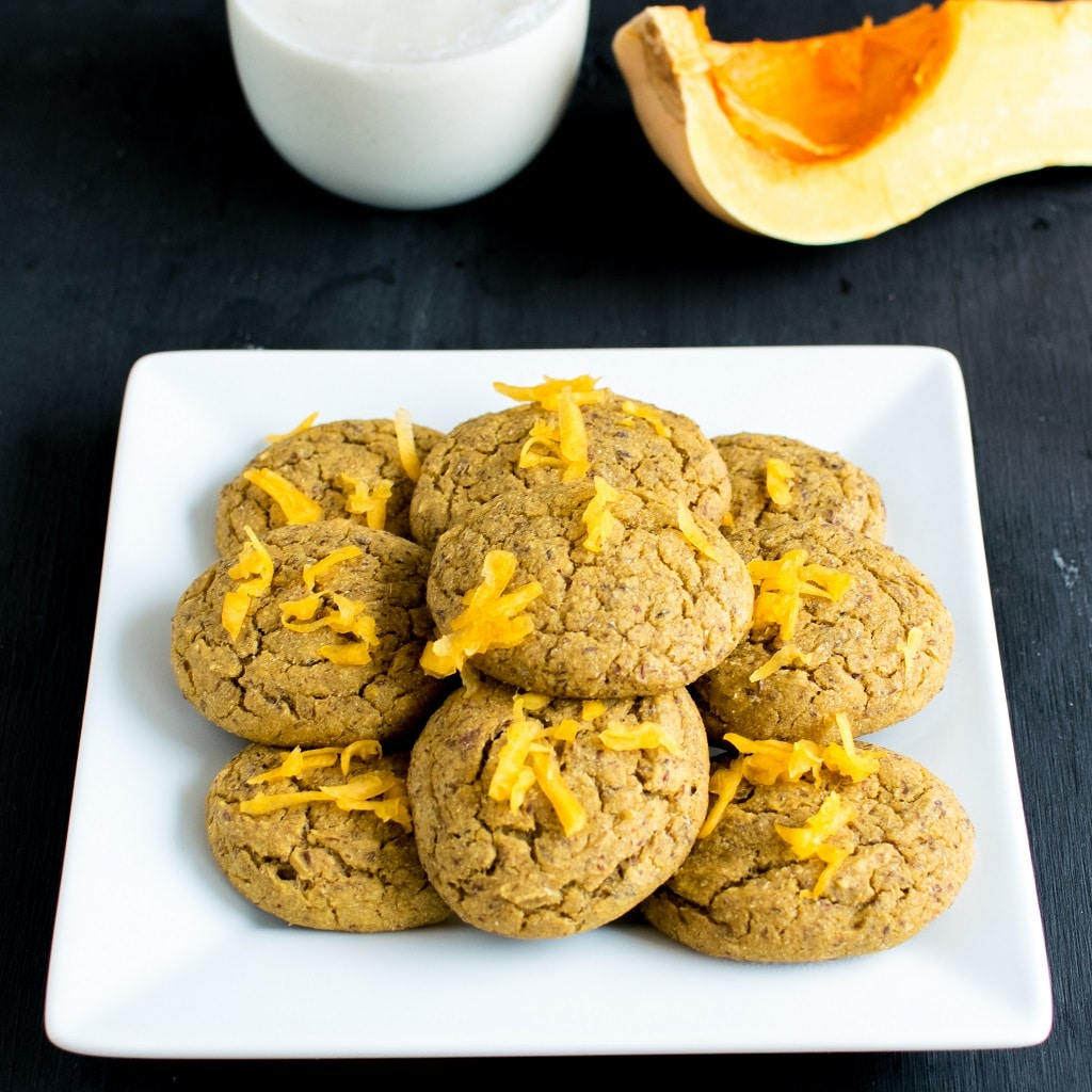 Butternut Squash Barley Vegan Cookies piled up in a square white plate with a glass of milk and fresh butternut squash at the background [ oil free + nut free ] kiipfit.com