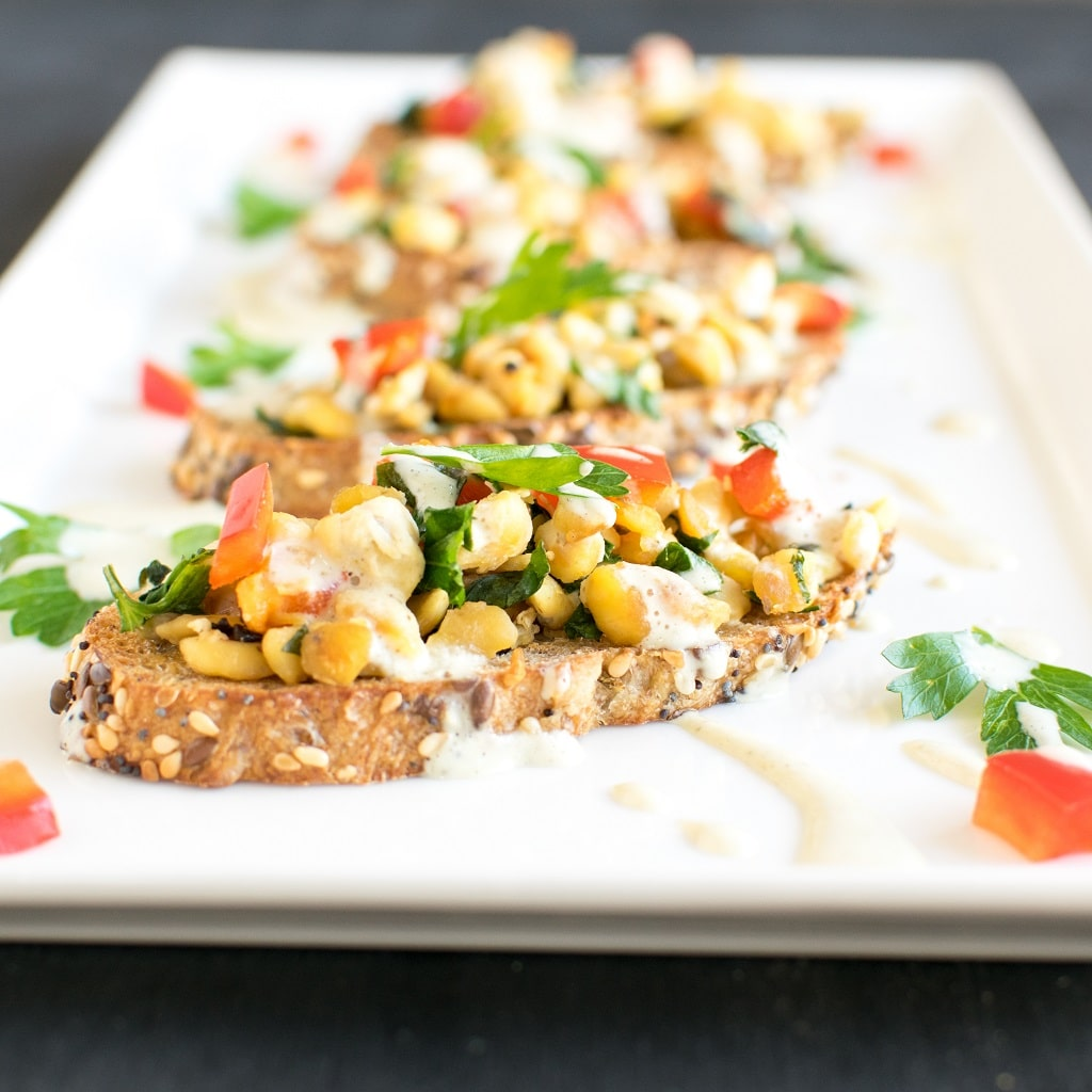 Herbed Cashew Cream Tempeh Crostini is not only healthy but is packed with flavor and outstanding taste. It's very easy to make and is a perfect party appetizer. With Thanksgiving and Christmas approaching this appetizer is definitely a winner. The delicious blend of herbs along with raw cashew nuts drizzled over tempeh crostini is to die for [ vegan ] kiipfit.com