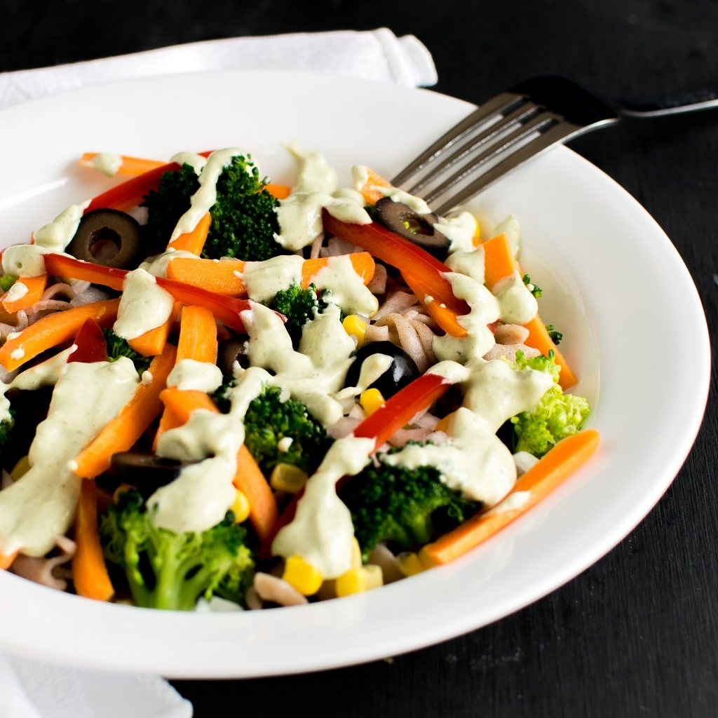 Jalapeno Tahini Vegan Pasta Salad in a white round bowl with a white table cloth as a prop. A fork is placed at the background as a prop too. The salad is covered with generous amount of dressing and is extremely colorful with green, orange red and many more veggies in it | kiipfit.com
