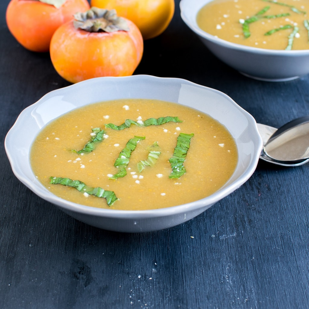 Persimmon Habanero Soup presented in two bowls as a mirror effect with fresh persimmons as prop at the background [ vegan + gf + paleo + oil free ] kiipfit.com