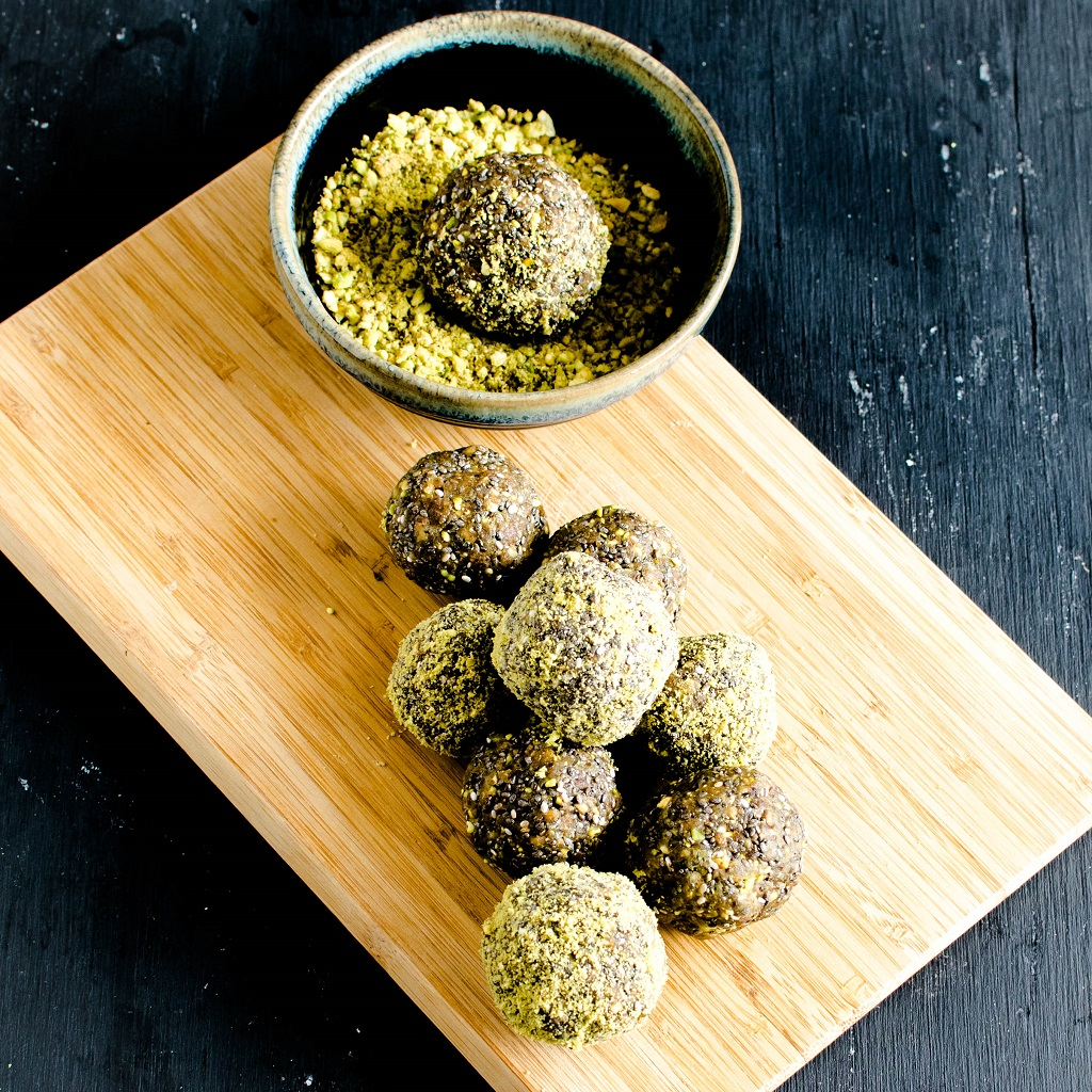 a stack of 3 ingredient pistachio chia energy bites are shown on a wooden board | kiipfit.com