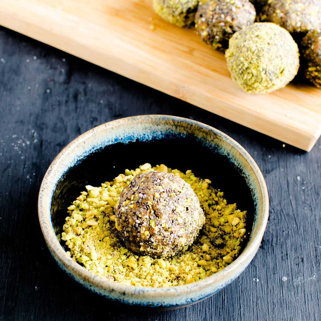 3 ingredient pistachio chia energy bites are shown in a bowl full of crushed pistachios. The energy bites are being rolled in the powdered pistachio | kiipfit.com