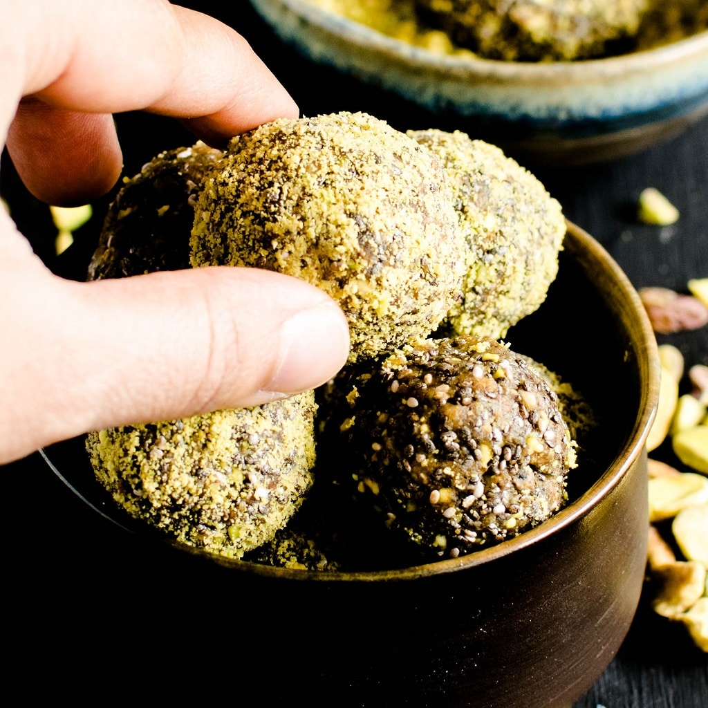 A hand in action to pick up one of the 3 ingredient pistachio chia energy bites is shown in this image | kiipfit.com