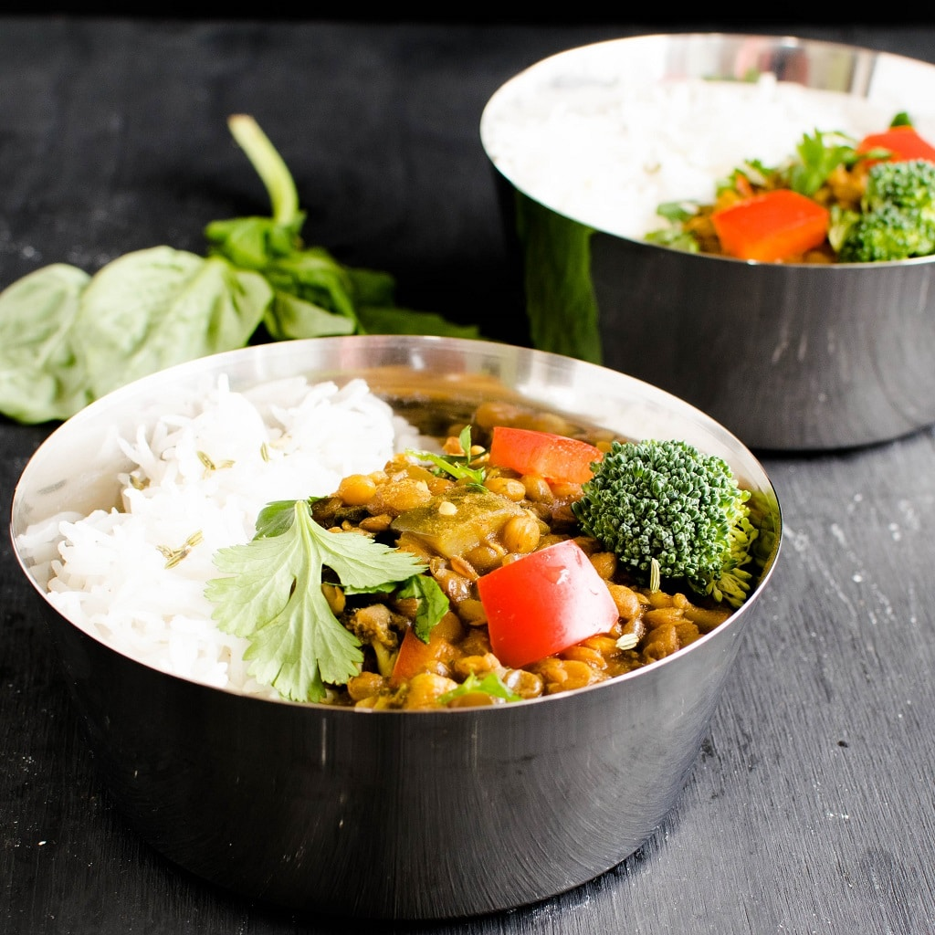 Two bowls full of Instant Pot Herbed Masala Lentil Curry along with steamed rice is shown in this image | kiipfit.com