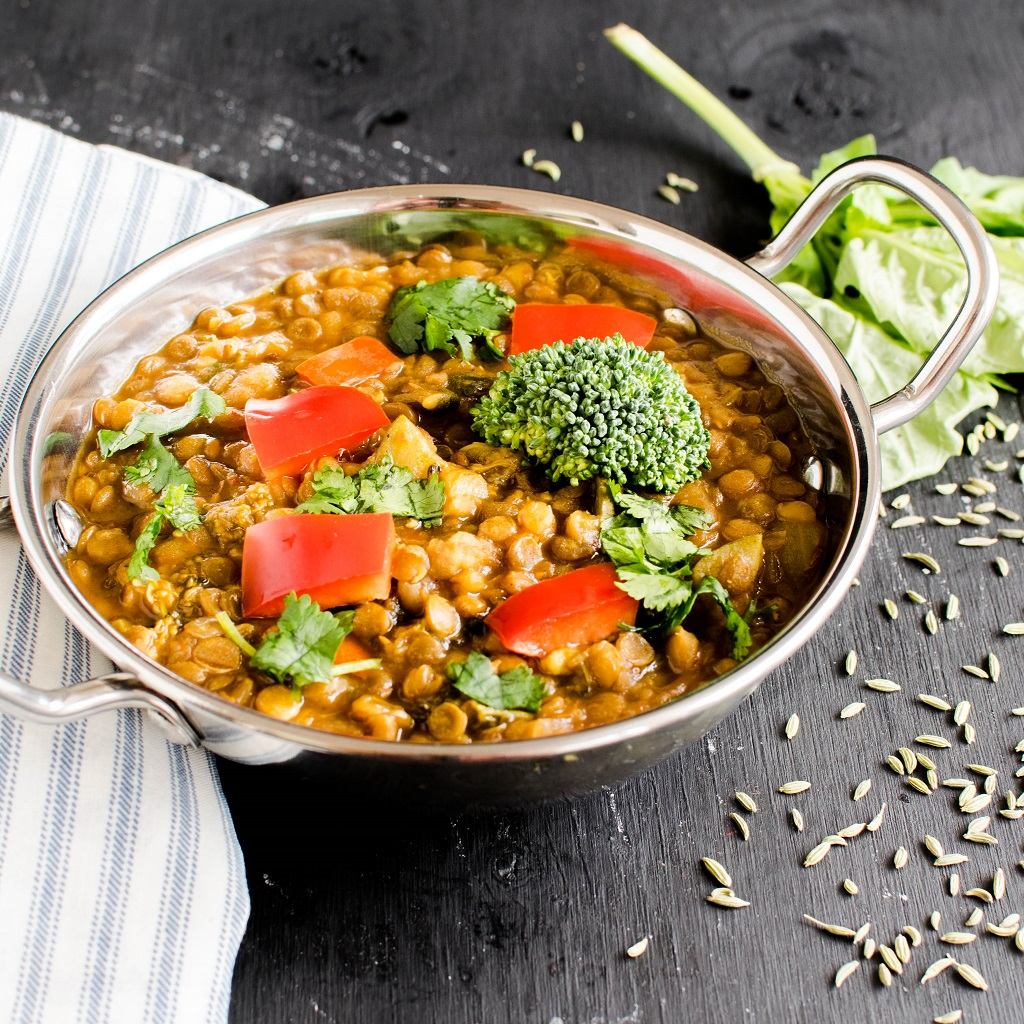 Instant Pot Herbed Masala Lentil Curry is shown in an indian kadhai with herbs and seeds as the prop | kiipfit.com