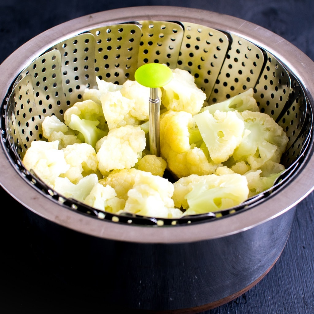 Steamed cauliflower florets are shown in a steamer basket placed inside a saucepan | kiipfit.com