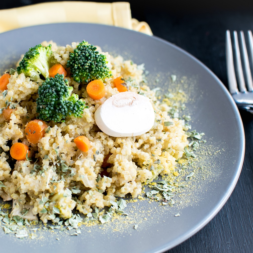 Pressure Cooker Vegan Cheese vegetable Quinoa is shown on a grey plate with a fork and a table cloth as the props | kiipfit.com