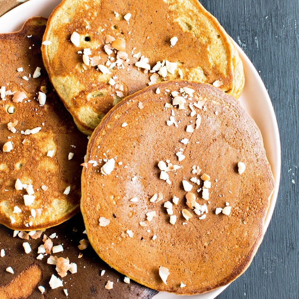 A plate full of chickpea flour peanut butter protein pancakes topped with peanuts in shown in this image | kiipfit.com