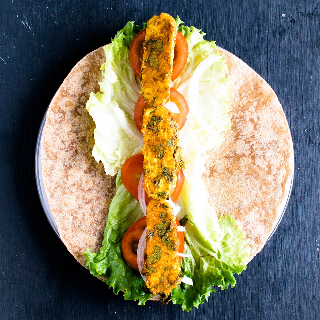 A whole grain tortilla with salad and cooked tempeh being in the process of forming a wrap is shown in this image.