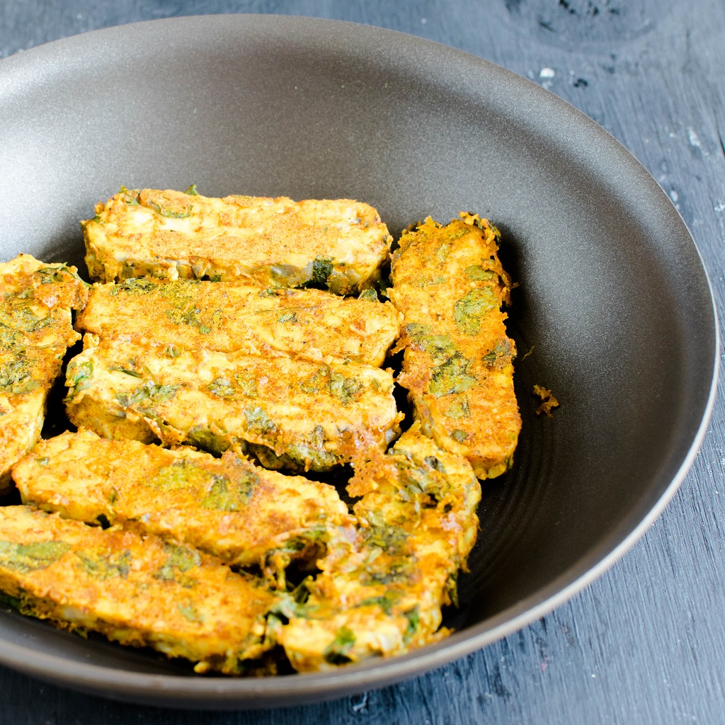 Cooked tempeh in a pan is shown in this image.