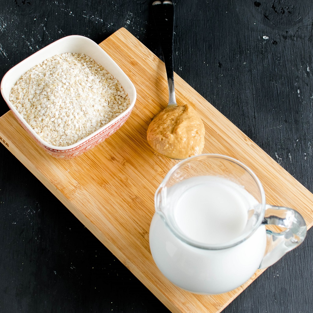 The raw ingredients of Peanut Butter Quinoa Flake Porridge on a wooden board is shown in this image | kiipfit.com