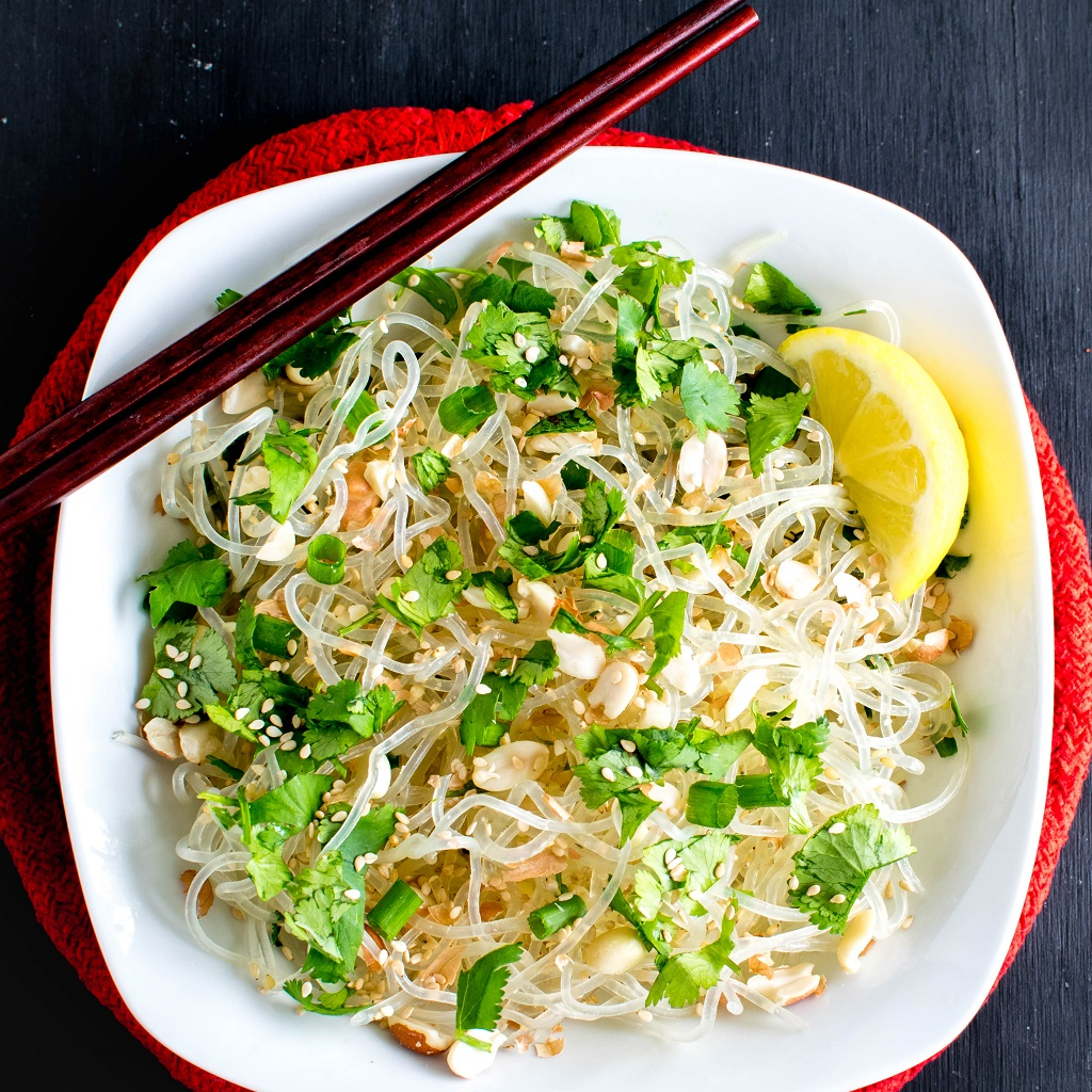 A white bowl full of Sesame Peanut Kelp Noodles Stir Fry Salad is shown with chopsticks as the prop | kiipfit.com