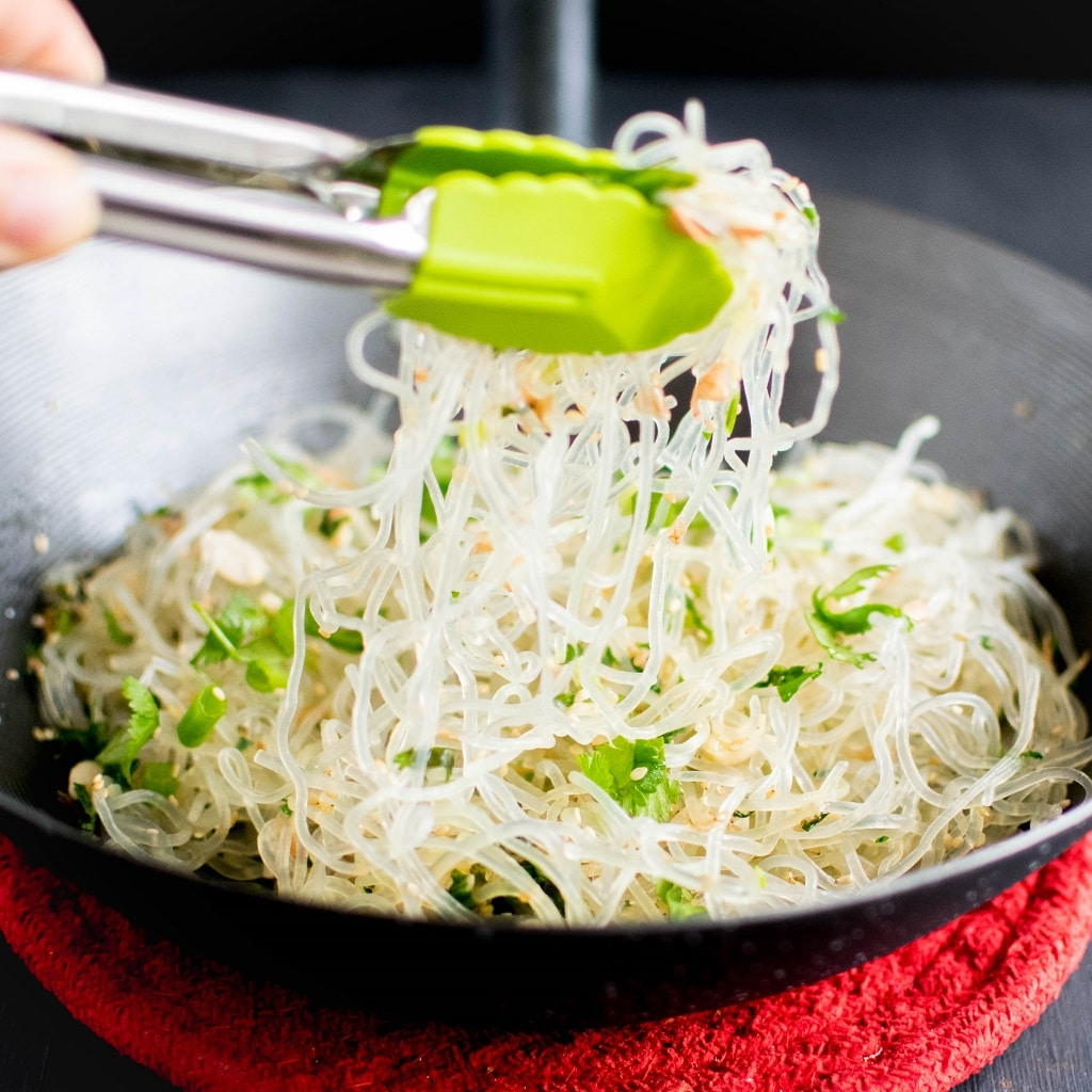 Kelp noodle is being tossed with the tongs in a wok | kiipfit.com