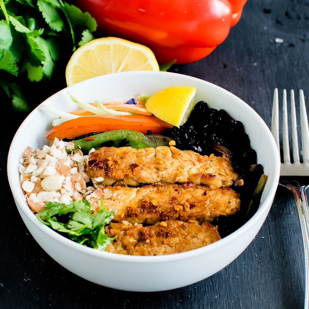 A complete recipe of black rice sriracha tempeh bowl in one serving bowl is shown in this image. The raw ingredients has been used as props in this picture | kiipfit.com