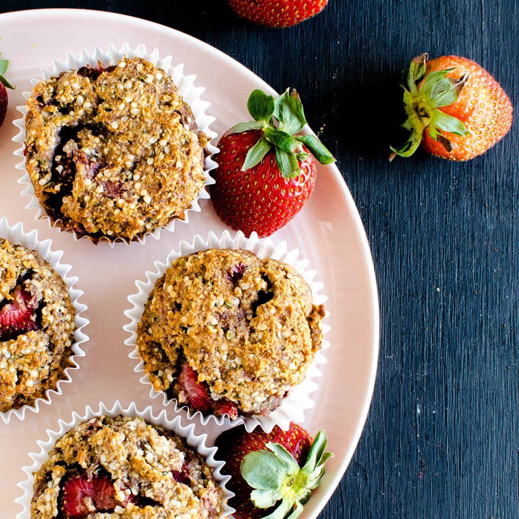 Strawberry Jam Vegan Protein Muffins are shown on a pink colcored round plate with fresh strawberries as the prop | kiipfit.com
