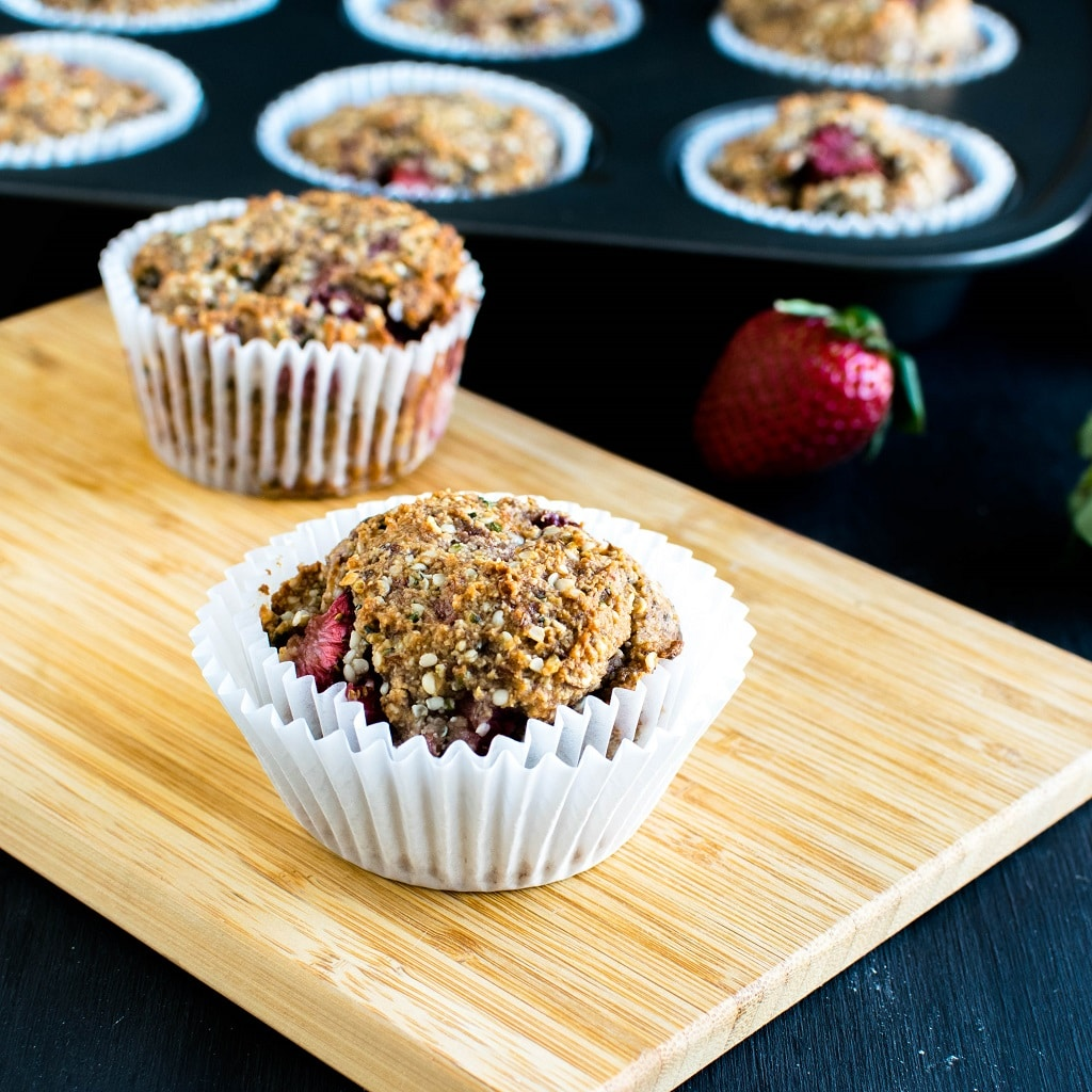 A wooden board is shown with strawberry jam vegan protein muffins and loaded muffin tray at the background | kiipfit.com