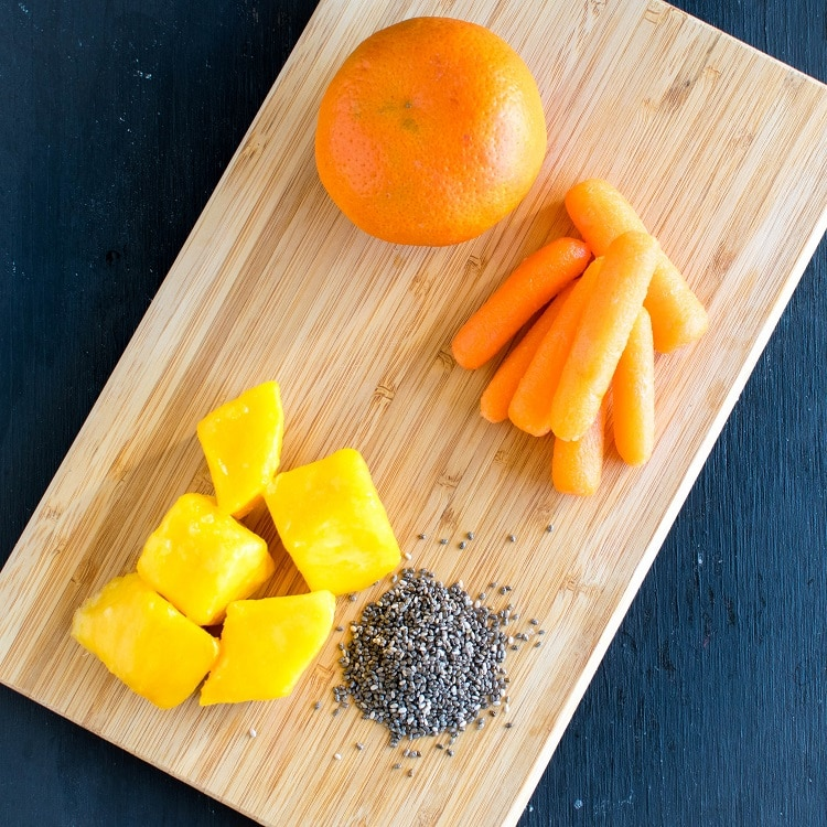 The raw ingredients of Carrot Orange Spring Smoothie is shown on a wooden board.