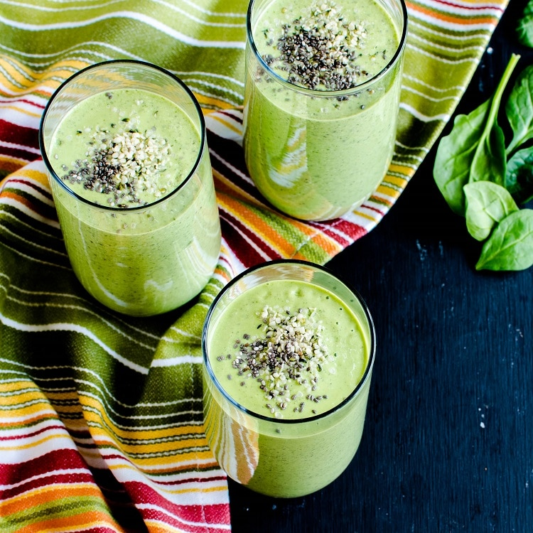 A top view of the table spread with smoothie glasses filled with Chia Hemp Green Smoothie and raw ingredients as prop is shown in this image.