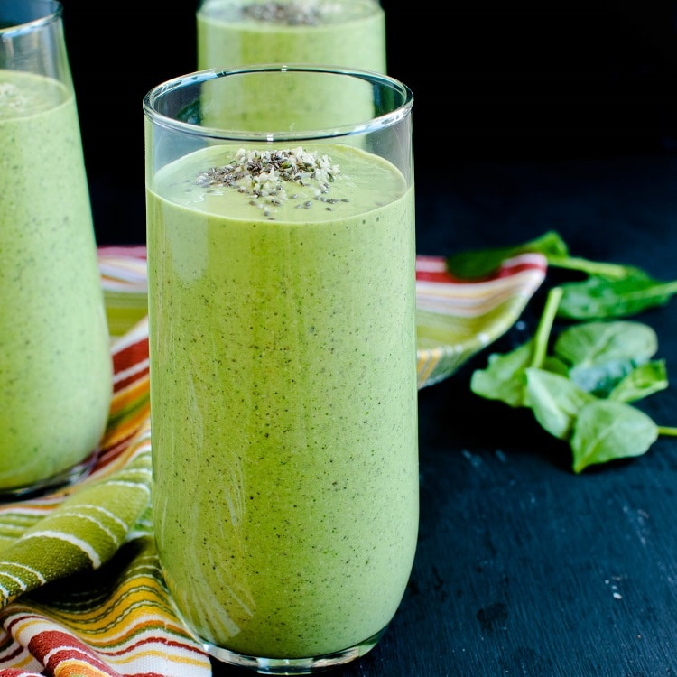 A close of a tall glass filled with Chia Hemp Green Smoothie is shown in this image.