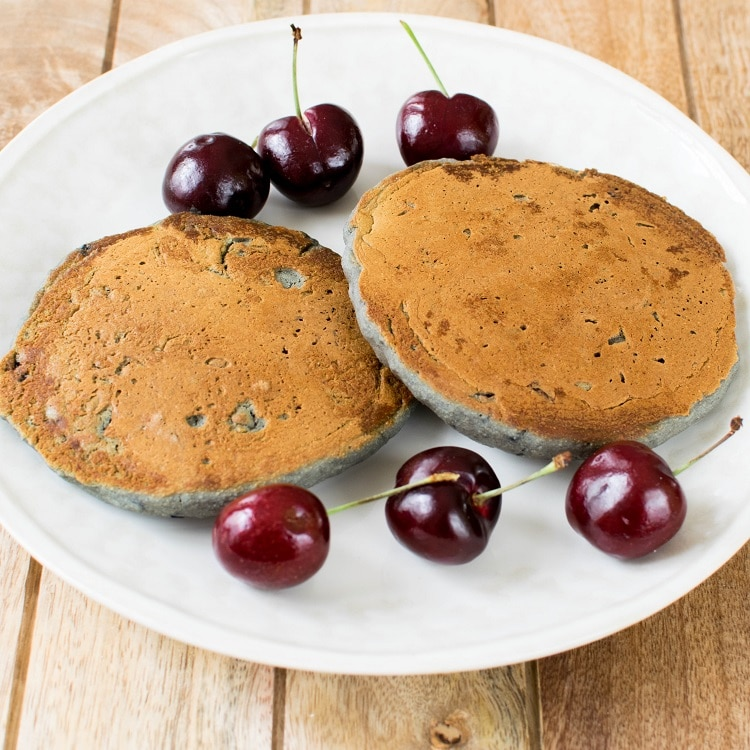 Cherry Oatmeal Pancakes are set on a plate immediately out of the pan.