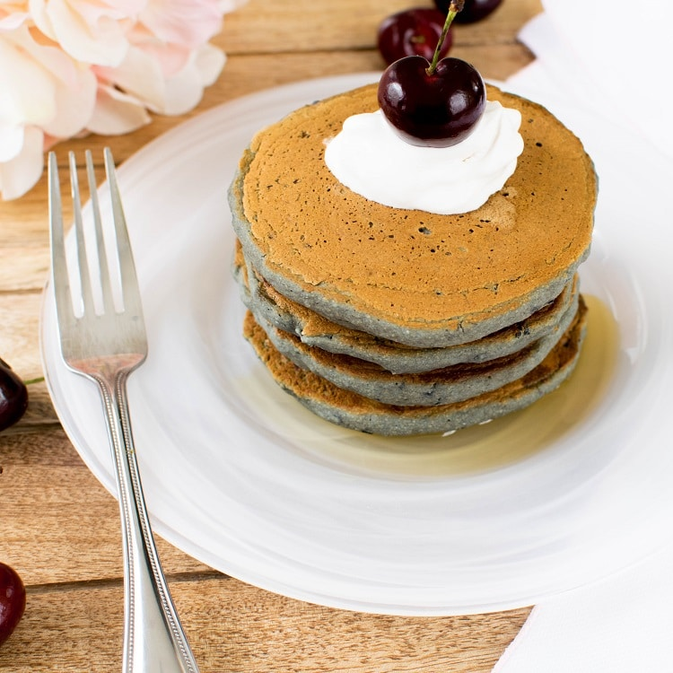 A stack of Cherry Oatmeal Vegan pancakes are shown in a wound white marble plate with whipped cream and a cherry on top