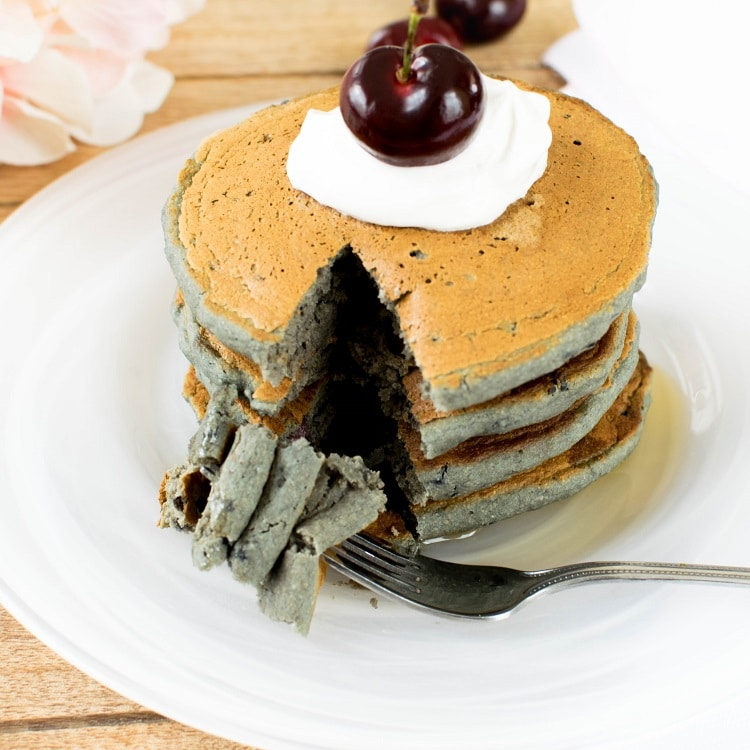 A portion oa the cherry oatmeal vegan pancakesis cut and stacked on the fork in this image.